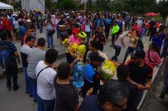 Кито, эквадор - 17-ое апреля 2016: Толпа людей Кито обеспечивая еду, одежды, медицину и воду гуманитарной помощи Стоковые Фото
