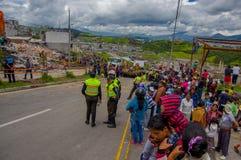 Кито, эквадор - 17-ое апреля 2016: Толпа людей смотря дом разрушенный землетрясением, и тяжелой техникой очищая disas Стоковое Изображение RF