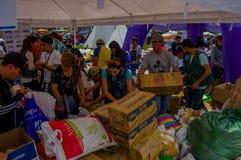 Кито, эквадор - 17-ое апреля 2016: Толпа людей смотря дом разрушенный землетрясением, и тяжелой техникой очищая disas Стоковое Фото