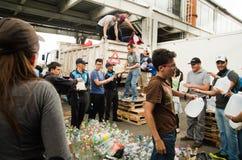 Кито, эквадор - 23-ье апреля 2016: Неопознанные граждане Кито обеспечивая еду гуманитарной помощи, одежды, медицину и Стоковое Фото