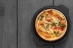 Киш лука томата и весны в блюде бака литого железа на древесине стоковые изображения rf