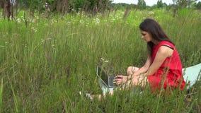Клавиатура молодой ультрамодной женщины печатая компьтер-книжка девушки снаружи используя видеоматериал