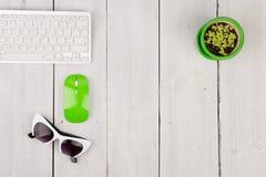 Клавиатура радиотелеграфа тонкая белая и зеленая мышь, стекла, цветок дальше Стоковое Изображение RF