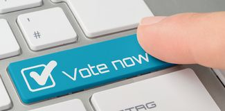 Клавиатура с голубой обозначенной кнопкой - голосованием теперь стоковая фотография rf