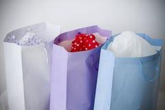кладет белизну в мешки покупкы голубой бумаги подарка пурпуровую Стоковая Фотография RF