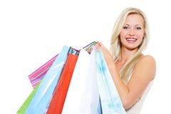 кладет белокурую смеясь над присутствующую женщину в мешки покупкы Стоковое Изображение