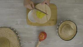 Кладет еду в блюдо с ножом На таблице 2 мексиканских шляпы, maracas, абстракция для instagram сток-видео