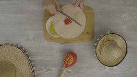 Кладет еду в блюдо с ножом На таблице 2 мексиканских шляпы, maracas, абстракция для instagram видеоматериал
