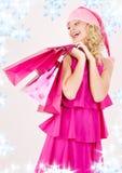 кладет жизнерадостную покупку в мешки santa хелпера девушки стоковые изображения rf
