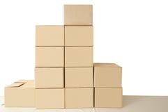 кладет картон в коробку Стоковые Изображения