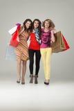 кладет красивейшее удерживание в мешки ходя по магазинам 3 женщины молодой Стоковые Изображения