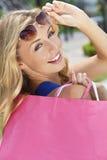 кладет красивейшую белокурую счастливую женщину в мешки покупкы Стоковая Фотография