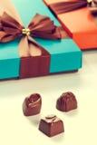 кладет подарок в коробку шоколадов Стоковое фото RF