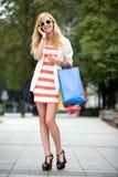 кладет покупку в мешки девушки стоковая фотография