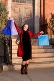 кладет счастливую покупку в мешки показывая детенышей женщины Стоковое фото RF