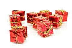 кладет тесемку в коробку красного цвета золота подарка Стоковые Фото