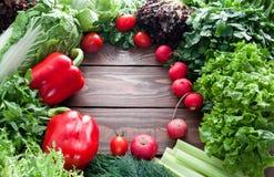 Кладут ассортимент зрелых красных овощей и зеленые цвета на деревянном столе вне на паз установьте текст стоковые фотографии rf