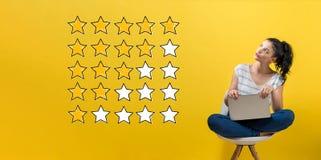 Классифицировать с желтыми звездами при женщина используя компьтер-книжку стоковые фотографии rf