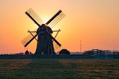Классическая голландская ветрянка, близко к городу Лейдена, Нидерланд, стоит ясно против оранжевого покрашенного неба стоковое изображение rf