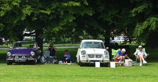 Классические автомобили и предприниматели имея пикник на зеленом цвете деревни Глашатый Truimph и автомобили MG стоковая фотография