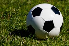 Классический футбольный мяч на предпосылке зеленой травы стоковые изображения