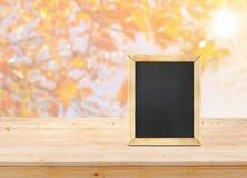 Классн классный на деревянной столешнице с кленовым листом нерезкости с солнечным светом Стоковые Фото