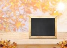Классн классный на деревянной столешнице с кленовым листом нерезкости с солнечным светом Стоковые Изображения