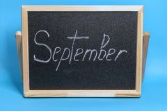 Классн классный со словом побелило сентябрь мелом на голубой предпосылке стоковое изображение rf