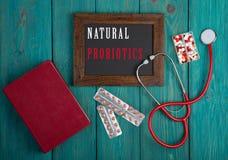 Классн классный с словом & x22; Естественное probiotics& x22; , стетоскоп, книга, пилюльки на голубой деревянной предпосылке стоковые изображения