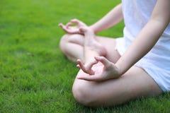 Класть азиатского китайца крупного плана лежа на лужайку травы думая для того чтобы сделать представление йоги в раздумье солнечн стоковая фотография rf