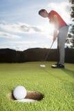 класть игрока в гольф чашки шарового подпятника стоковое фото