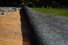 Класть искусственную дерновину травы на песок Стоковая Фотография