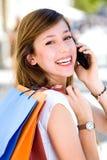 кладет покупку в мешки мобильного телефона девушки Стоковые Изображения RF