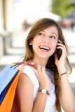 кладет покупку в мешки мобильного телефона девушки Стоковое фото RF