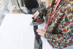 Клеить ткань с помощью утюгу Шов работает с тканью на утюжа таблице стоковые изображения