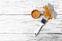 Кленовый лист падения желтые сухие, щетка и краска золота на белой деревянной предпосылке Цвета осени, творческие способности, се стоковое изображение rf