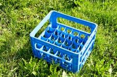 Клеть бутылки пива пустая пластичная на траве Стоковая Фотография