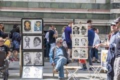 Клиенты каррикатуриста сидя ждать в аркаде del Duomo, позади, туристы и часть стены собора стоковое фото