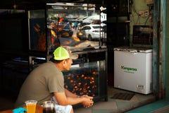 Клиенты продавца рыбки ждать и выпивая пиво Стоковые Фото