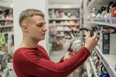 Клиент выбирает чайник в моле супермаркета, трудном решении стоковые фото