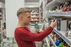 Клиент выбирает чайник в моле супермаркета, трудном решении стоковая фотография rf