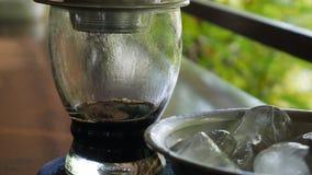 Клиент выпивает ожидания холодного чая заваривая черный кофе используя въетнамский традиционный фильтр phin в кафе Потеки кофе видеоматериал