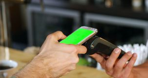 Клиент делая оплату через мобильный телефон на встречном 4k сток-видео