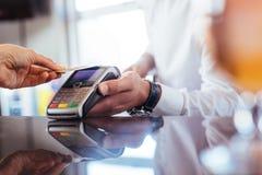 Клиент используя технологию NFC для оплаты на баре Стоковая Фотография