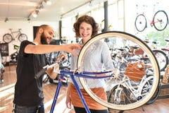 Клиент и торговец в магазине велосипеда - купите и ремонт велосипедов - обслуживание клиента стоковые фото