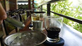 Клиент кладет лед в черный кофе перед выпивать Используя въетнамский традиционный фильтр phin в кафе Вертеп da phe Ca сток-видео