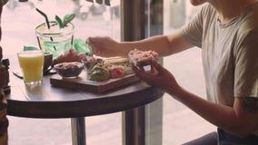 Клиент на кафе наслаждается здравицей с авокадоом акции видеоматериалы