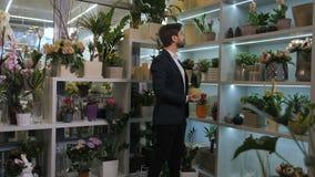 Клиент салона Floristical выбирая в горшке цветки сток-видео
