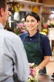 Клиент сервировки женщины в florist стоковое фото rf