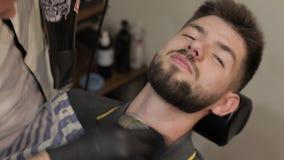 Клиент с черной бородой во время бороды брея в парикмахерской Выхольте, мужеский сток-видео